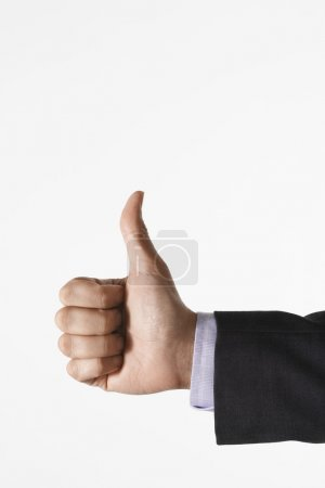 Photo for Man making thumbs-up sign against white background close up of hand - Royalty Free Image