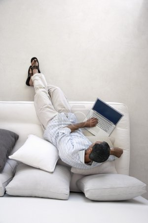 Photo for Man using laptop sitting on sofa in living room - Royalty Free Image