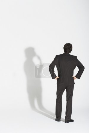 Businessman arguing with own shadow