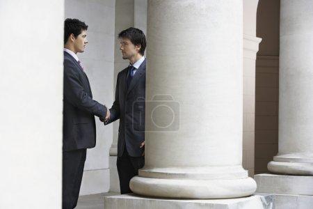 Photo pour Deux hommes d'affaires se serrant la main à l'extérieur de l'édifice par le pilier - image libre de droit