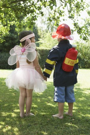 Girl and boy in fairy and fireman costumes