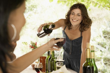 women with wine at dinner party