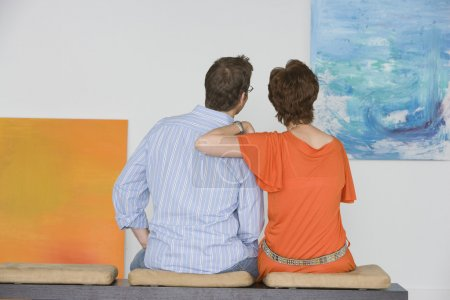 Couple observing painting