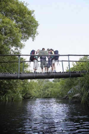 teenagers reading map on bridge