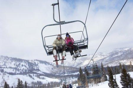 Couple in skies sitting on ski lift