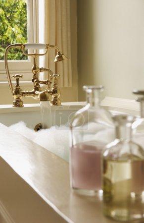 Photo pour Huiles naturelles dans des bouteilles sur la baignoire remplis de bain moussant - image libre de droit