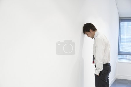 Unhappy Businessman with head against wall