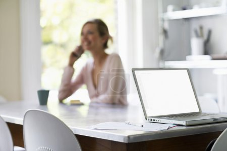 Photo pour Femme sur téléphone assis à la table de la cuisine par focus portable sur ordinateur portable - image libre de droit