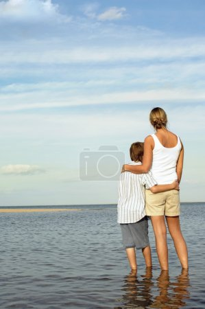 Photo for Mother and Son standing in water by shore of Beach looking at view back view - Royalty Free Image