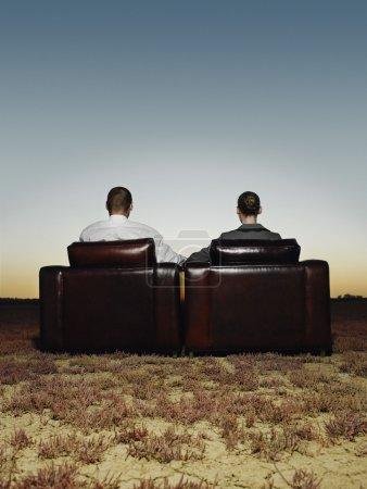 Photo pour Deux hommes d'affaires dans des fauteuils en plaine ouverte au coucher du soleil vue arrière - image libre de droit