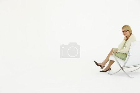 Photo pour Femme d'affaires assise sur une chaise sur fond blanc - image libre de droit