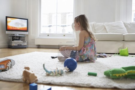 Girl sitting on floor watching television