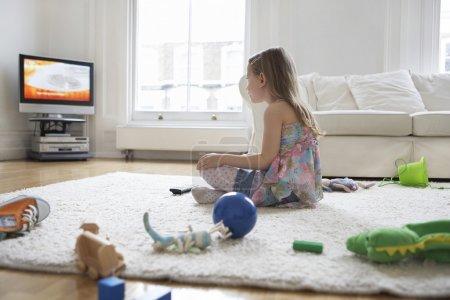 Photo pour Fille assise sur le sol entouré de jouets regarder la télévision - image libre de droit