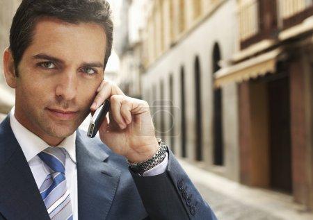 Photo pour Homme d'affaires dans la rue à l'aide de téléphone mobile gros plan portrait . - image libre de droit