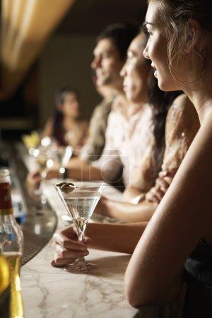 Photo pour Jeunes debout au comptoir Bar avec des cocktails vue latérale - image libre de droit
