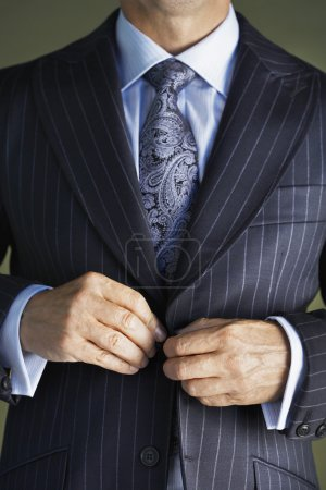Businessman buttoning buttons on jacket