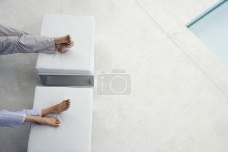 Feet on foot stools by swimming pool