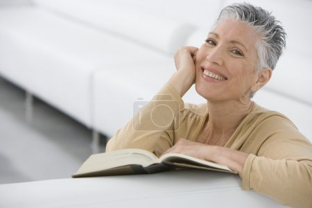 Photo for Middle-aged woman reading book on sofa - Royalty Free Image