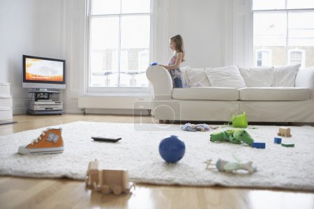 Photo for Girl  watching television, toys on floor in foreground - Royalty Free Image