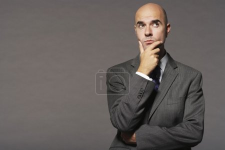 Bald businessman with hand on chin