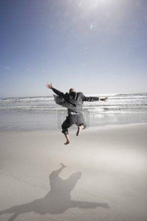 Enthusiastic Businessman Jumping on the Beach