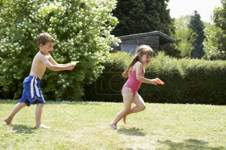 Boy shooting girl with water pistol