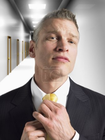 Man adjusting tie in corridor