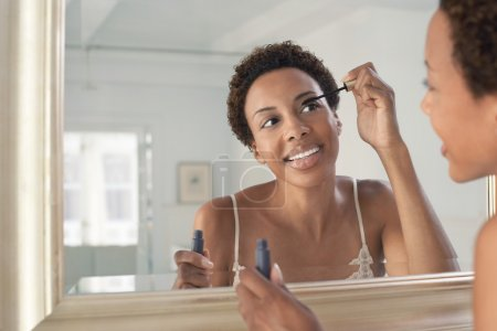 Woman applying mascara in mirror