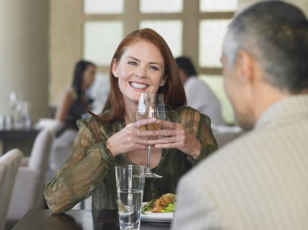 Woman smiling at man in restaurant