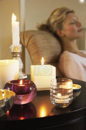 Photo pour Femme reposante sur le canapé à côté de la table avec des bougies - image libre de droit