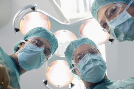 Surgeons preparing to operate in operating theatre