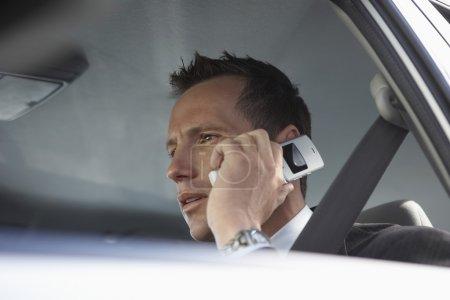 Businessman using mobile phone in car