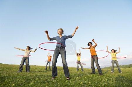 Photo pour Jeunes femmes adultes à l'aide de cerceaux en plein air - image libre de droit