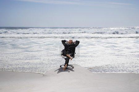 Photo pour Homme d'affaires assis dans une chaise de bureau sur la plage - image libre de droit