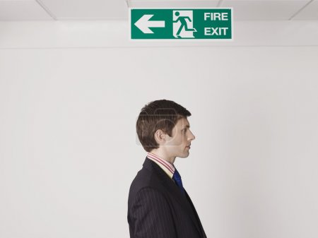 Businessman standing under exit sign