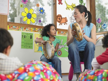 Teacher playing Tambourines with child