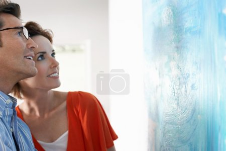Photo for Couple looking at modern art painting in gallery - Royalty Free Image