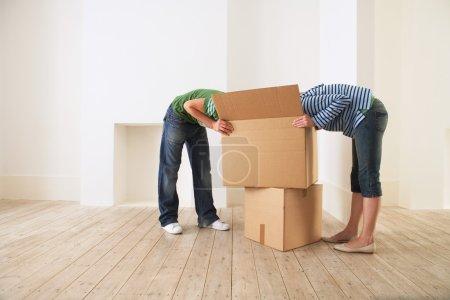 Photo pour Boîte de déballage jeune couple dans une nouvelle maison avec des visages cachés - image libre de droit