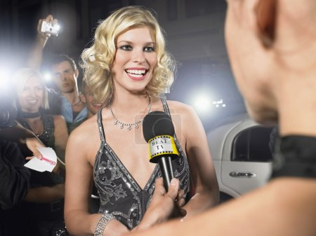 Photo for Woman talking into microphone on red carpet - Royalty Free Image