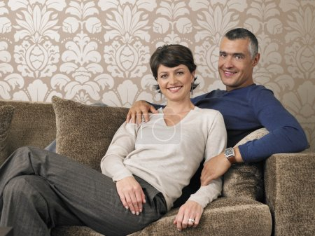Photo for Portrait of happy couple sitting on sofa - Royalty Free Image