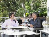 Two men talking at cafe