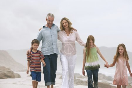 Family with children walking on beach