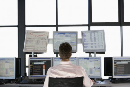 Businessmen watching computer screens