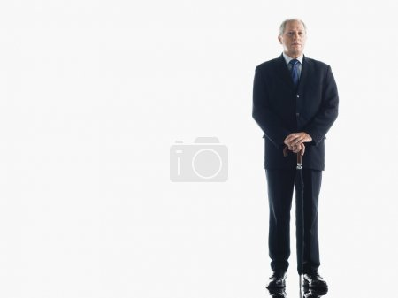 Businessman leaning on umbrella