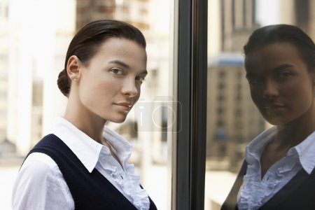 Woman standing reflected in window