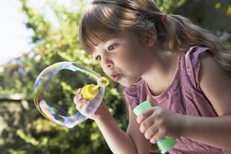 Girl Blowing Soap Bubble
