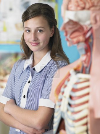 Student standing by anatomical model