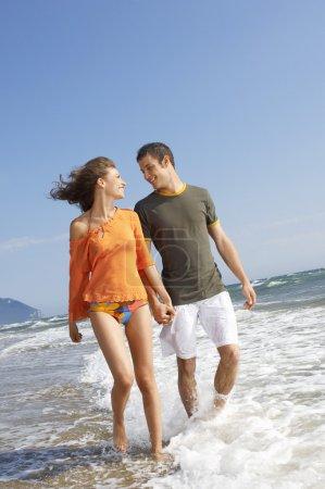 Couple walking through surf