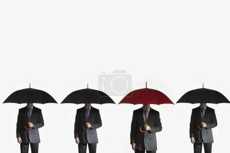 Businessmen holding umbrellas
