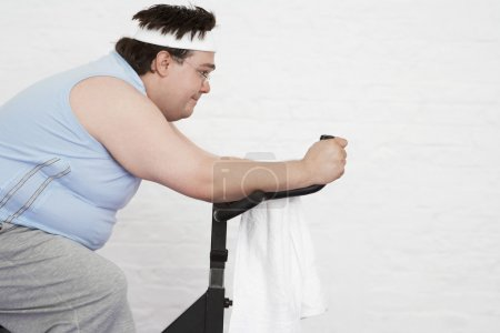 Photo for Overweight man on Exercise Bike side view - Royalty Free Image